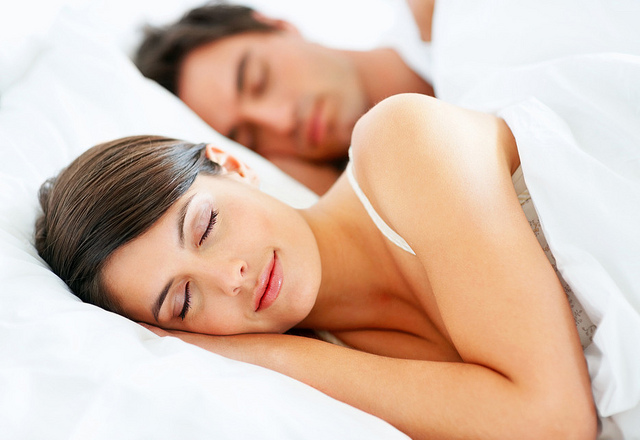 Beautiful young lady sleeping with husband on bed