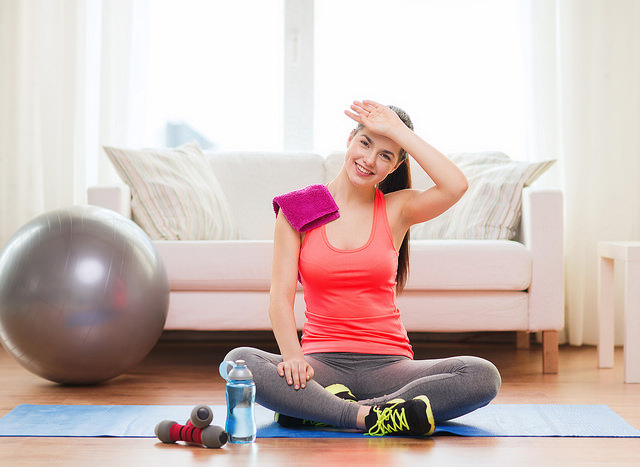 smiling girl with bottle of water after exercising