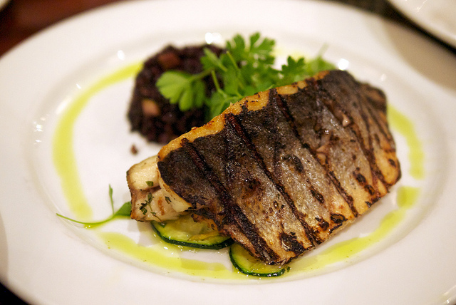 "BRANZINO E ZUCCHINE, Grilled Mediterranean seabass filet or whole with zucchine ""trifolate"" garlic thyme sauce, black ""venere"" rice"